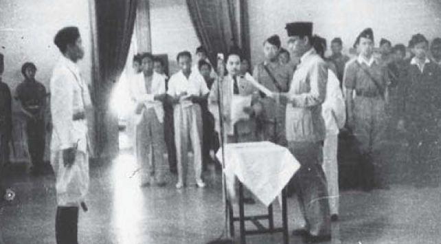 melantik pucuk pimpinan Tentara Nasional Indonesia di Istana Kepresidenan di Yogyakarta, 28 Juni 1947, dengan Jenderal Sudirman sebagai Panglima Besar. Sri Sultan Hamengkubuwono IX tampak di latar belakang, depan Presiden.