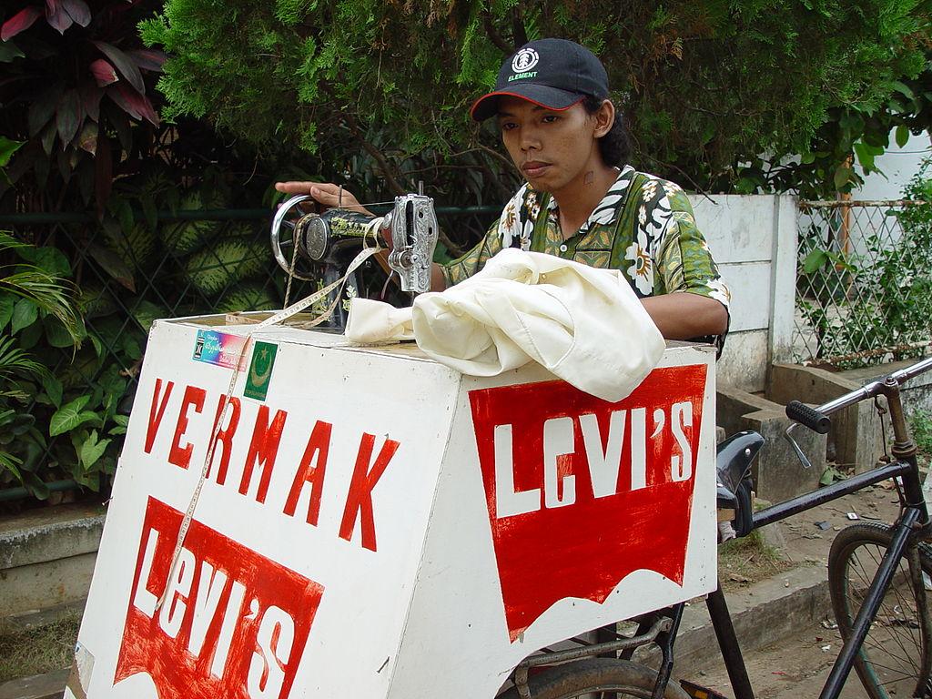 Jasa vermak levis (celana jeans) menggunakan sepeda.