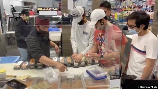 Nur Cholis (kiri) bersama anak-anak muda anggota IMAAM Center memberi label pada 100 kotak sushi (dok: Nur Cholis/IMAAM Center)
