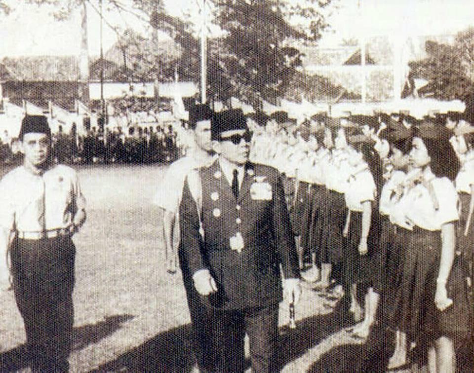 Sukarno meninjau barisan anggota pramuka pada acara pelantikan Gerakan Pramuka.