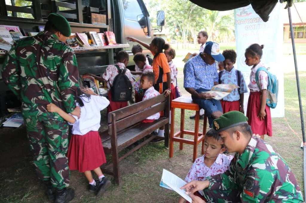 Para siswa di perbatasan Indonesia-Papua Nugini memanfaatkan perpustakaan keliling. (Foto: Penerangan Divisi 2 Kostrad)