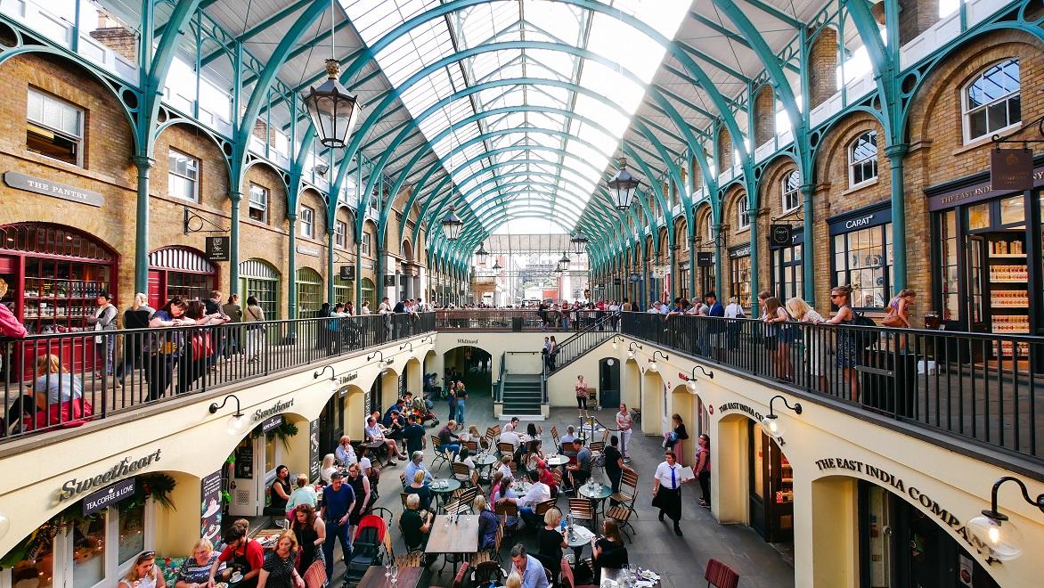 Tampilan dalam Covent Garden Market di London dengan jejeran kios di sisi kanan dan kiri dan foodcourt di lantai dasar.