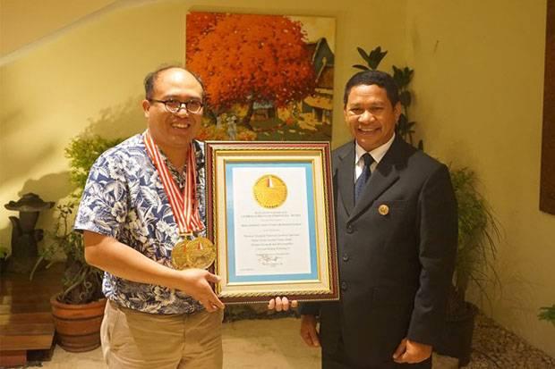 Prof Josaphat Tetuko Sri Sumantyo, Ph.D (kiri) memperlihatkan penghargaan Lembaga Prestasi Indonesia Dunia bersama Direktur Utama Leprid Paulus Pangka.