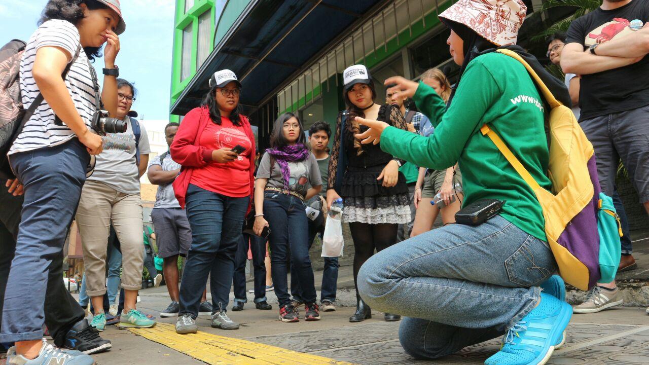 Suci Rifani (berbaju merah) menyimak penjelasan tentang hak dan kewajiban pengguna trotoar. © ITDP