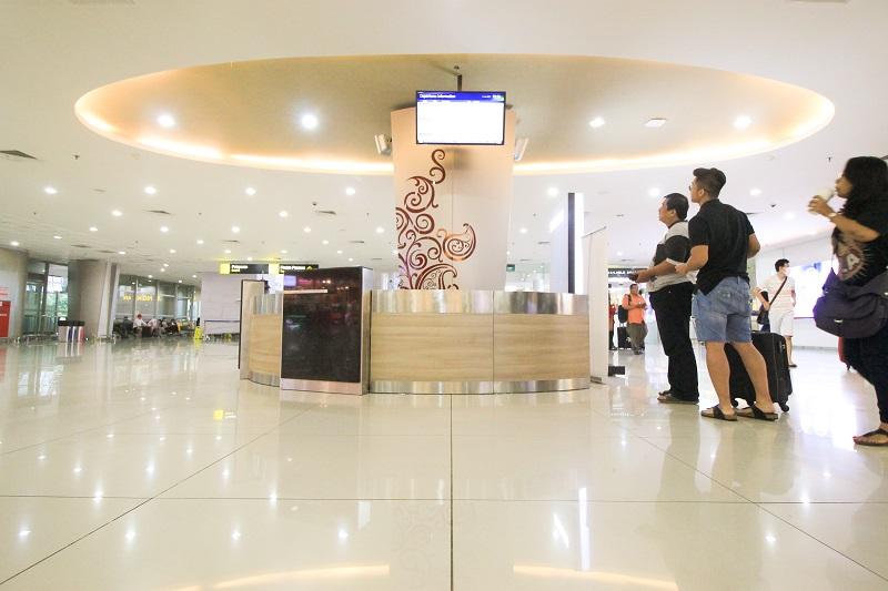 Dua orang pengunjung Bandara Juanda mengecek jadwal penerbangan di layar (foto: Afrizal/GNFI)