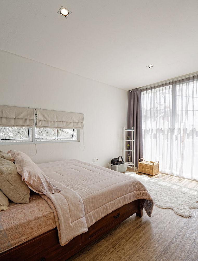 Jendela besar pada kamar tidur utama memungkinkan cahaya matahari yang masuk cukup untuk menerangi ruangan di siang hari (foto: architize)