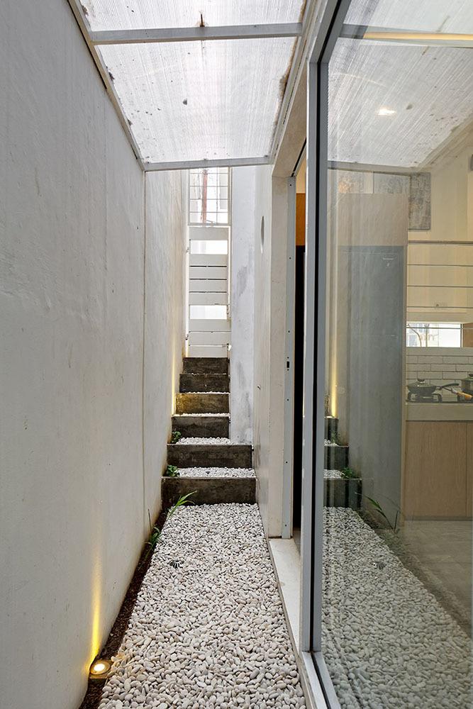 Halaman sempit di samping rumah memungkinkan sirkulasi udara yang masuk cukup untuk menyejukkan rumah (foto: architize)