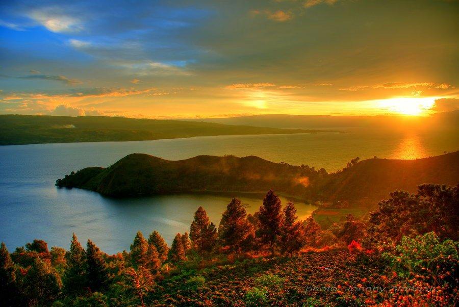 Air di Danau Toba menjad cermin pantulan cahaya sang fajar