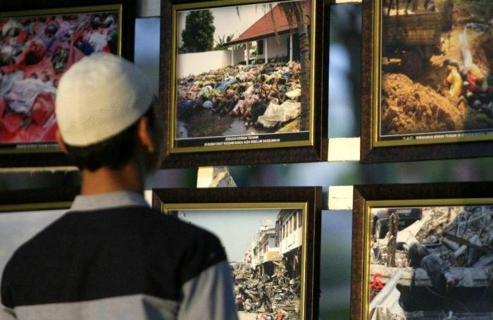 seorang pengunjung mengamati foto-foto evakuasi korban tsunami saat peringatan 11 tahun gempa dan tsunami di pemakaman massal Ulee Lheue, Banda Aceh (26/12/2015) © Hotli Simanjuntak /EPA | sumber : beritagar