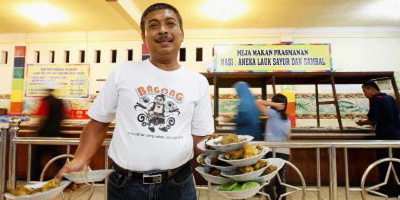 Rusdi, pemilik Rumah Makan Taman Selera di jalur pantura, Indramayu, Jawa Barat menunjukkan keahlian bawa piring banyak | sumber: KOMPAS/RONY ARIYANTO NUGROHO