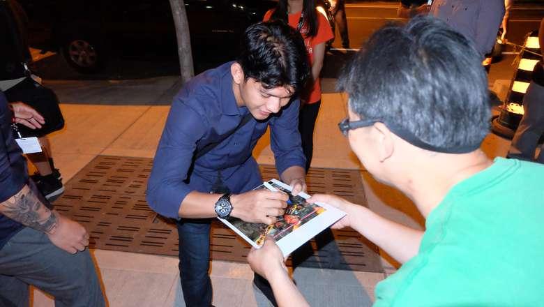 Iko Uwais membagikan tanda tangan untuk para penggemarnya | sumber foto: hot.detik.com