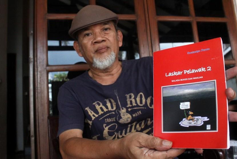 Soetantyo Moechlas dan bukunya yang bercerita tentang Mukidi dan Wakijan (Foto: Risky Andrianto / ANTARA)