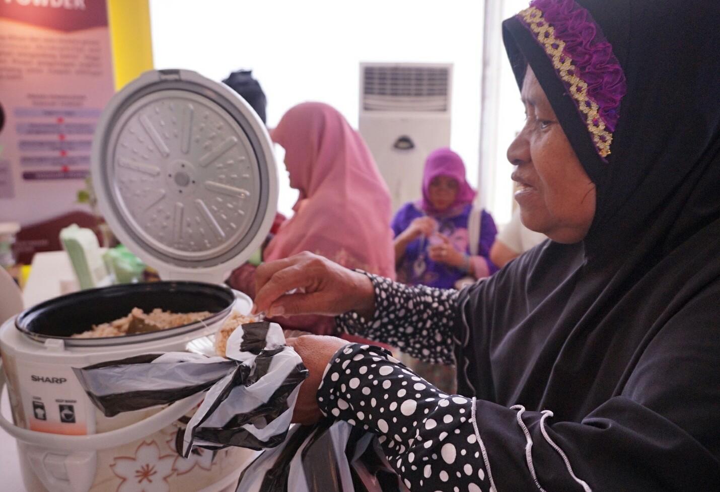 Seorang pengunjung saat mencicipi nasi jagung di HPS ke-36 (Foto: Bagus DR / GNFI)