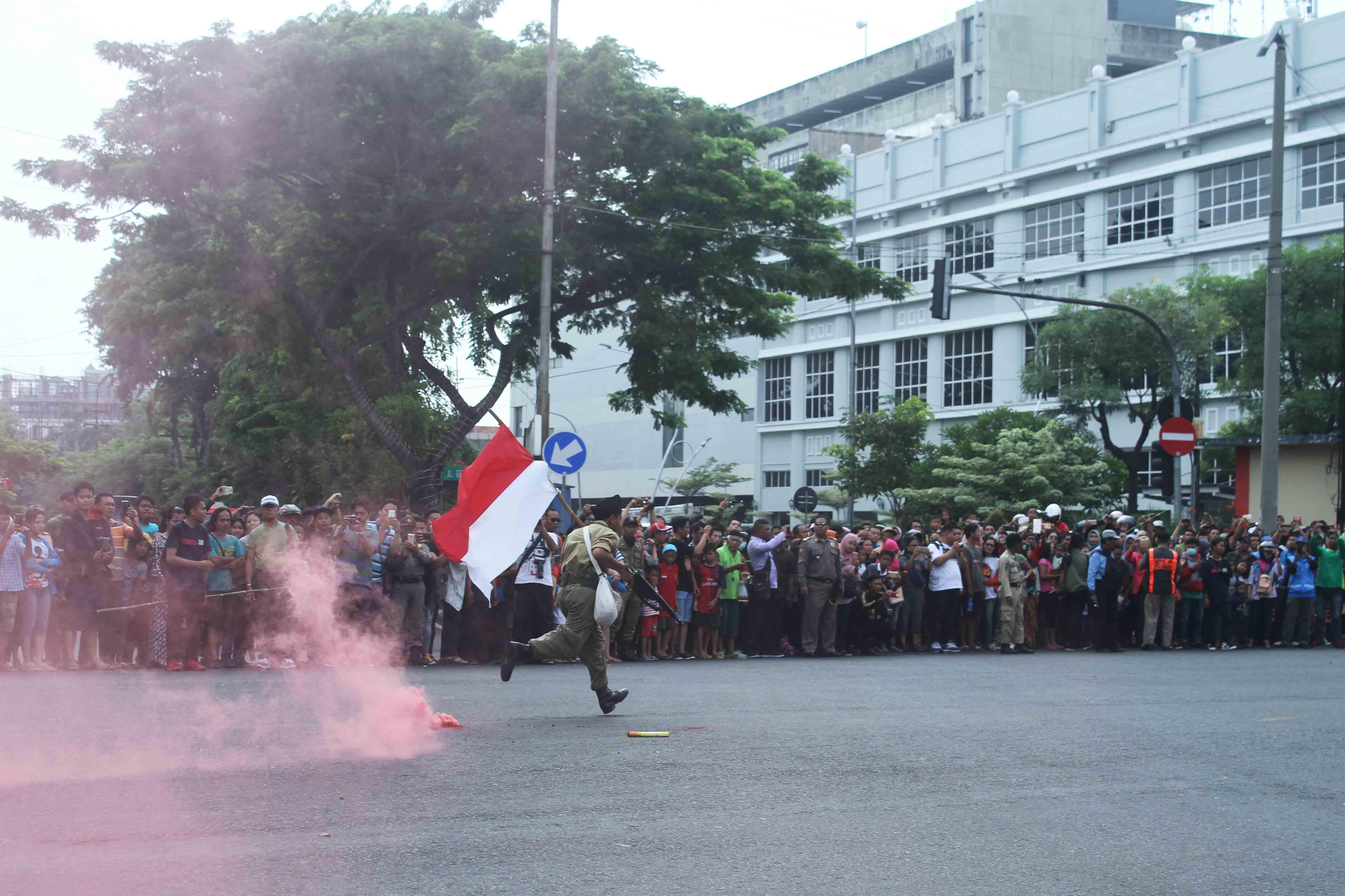 Seorang pejuang berlari membawa bendera Indonesia saat Parade Surabaya Juang