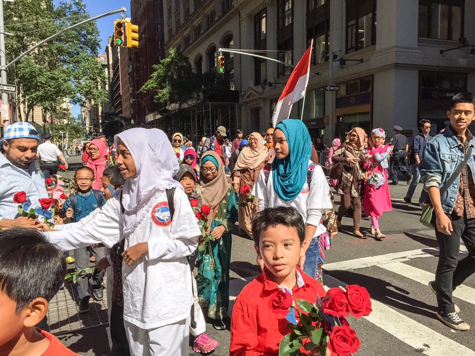 Anak-anak dan remaja muslim Indonesia membagikan bunga kepada penonton