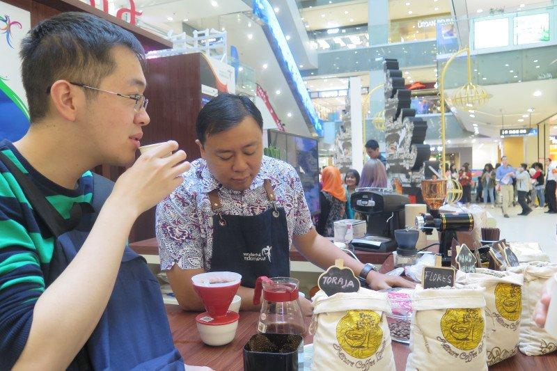 Pengunjung Pameran Wisata Indonesia di Beijing, China, mencicipi kopi khas Nusantara. Foto: ANTARA/M. Irfan Ilmie