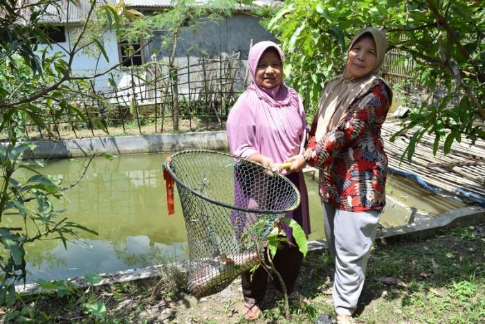 Enok Salamah (kiri) dan Aan (kanan) beserta ikan lele hasil tangkapan. Ternak lele merupakan salah satu proyek IOM untuk memberdayakan para penyintas perdagangan manusia di Sukabumi © Beh Lih Yi (via Reuters)
