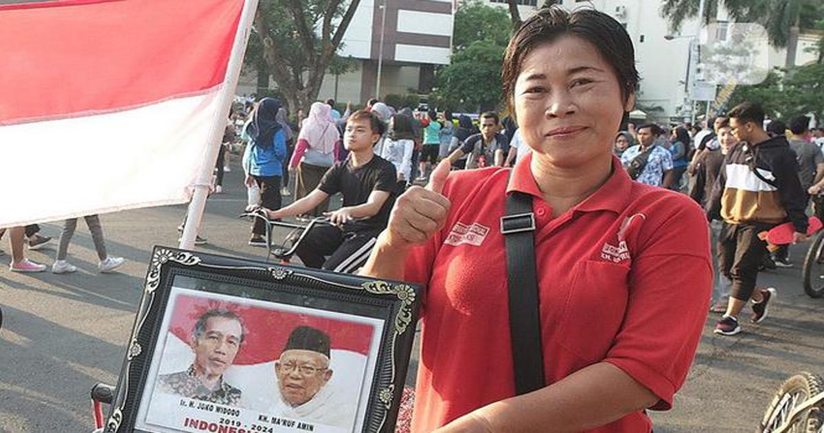 Seorang ibu yang berkeliling sepeda sambil membawa foto presiden Jokowi-Amin @Antaranews.com