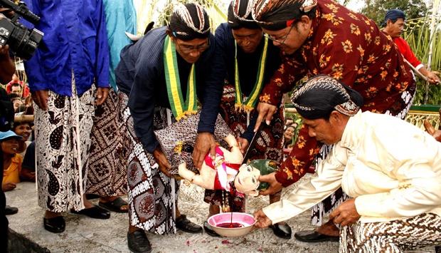 Sepasang pengantin yang dipersembahkan, sebagai simbol permohonan keselamatan (tempo.co)