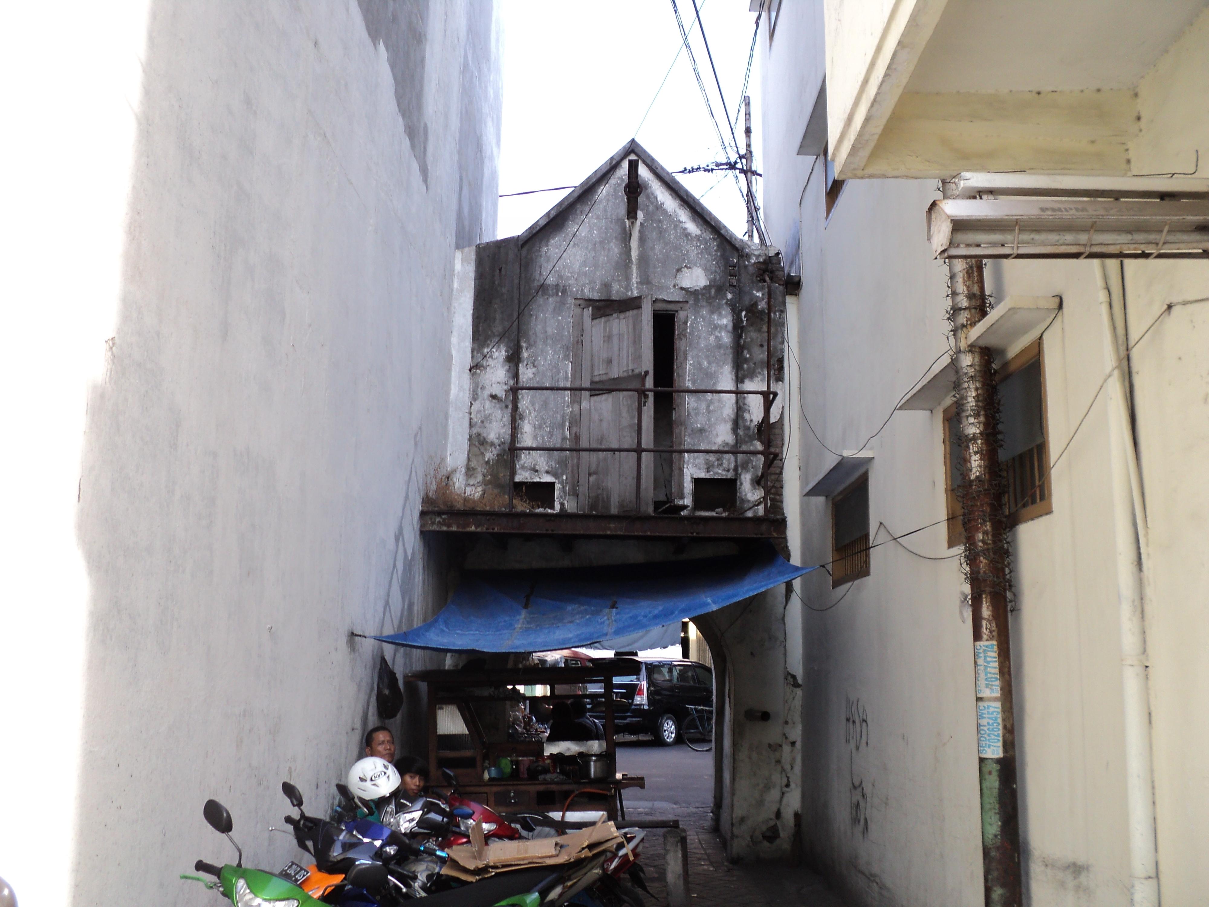 tampak belakang dari sebuah bangunan yang diyakini sebagai gerbang Keraton Surabaya. Bangunan tersebut kini diapit oleh pertokoan. (sumber foto: pesonacagarbudayasurabaya.wordpress.com)