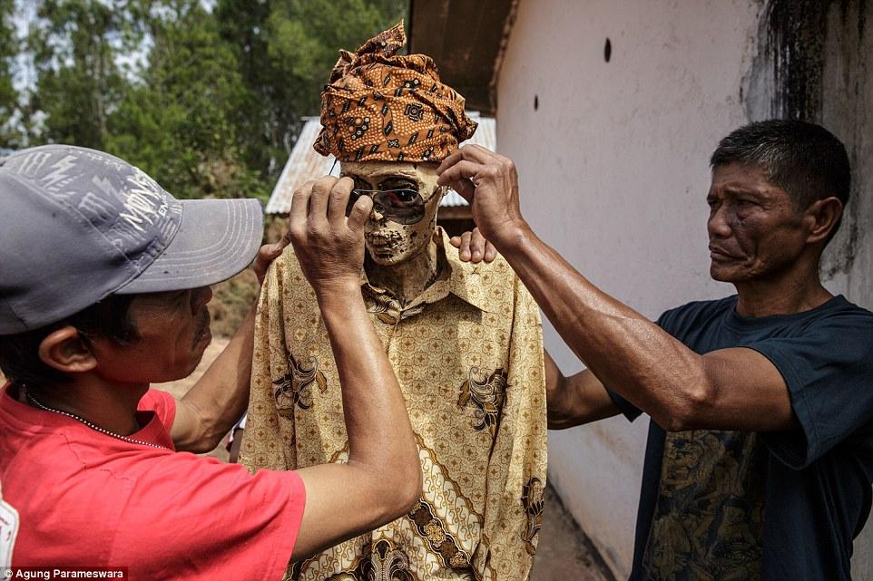 Tidak hanya diganti pakaiannya, jasad leluhur juga dirias mengenakan kaca mata hitam (photo credit: Agung Parameswara)