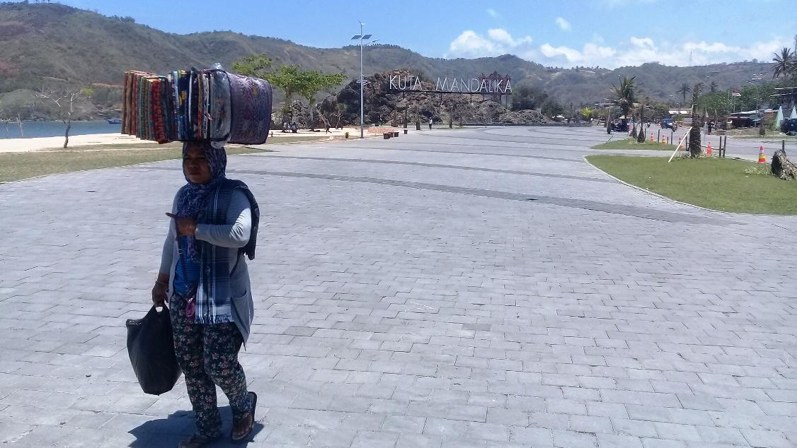 Seorang pedagang kain tenun Lombok berjalan di kawasan pantai Kuta Mandalika, KEK Mandalika, Lombok Tengah, NTB. Foto: Dok. Panca Nugraha