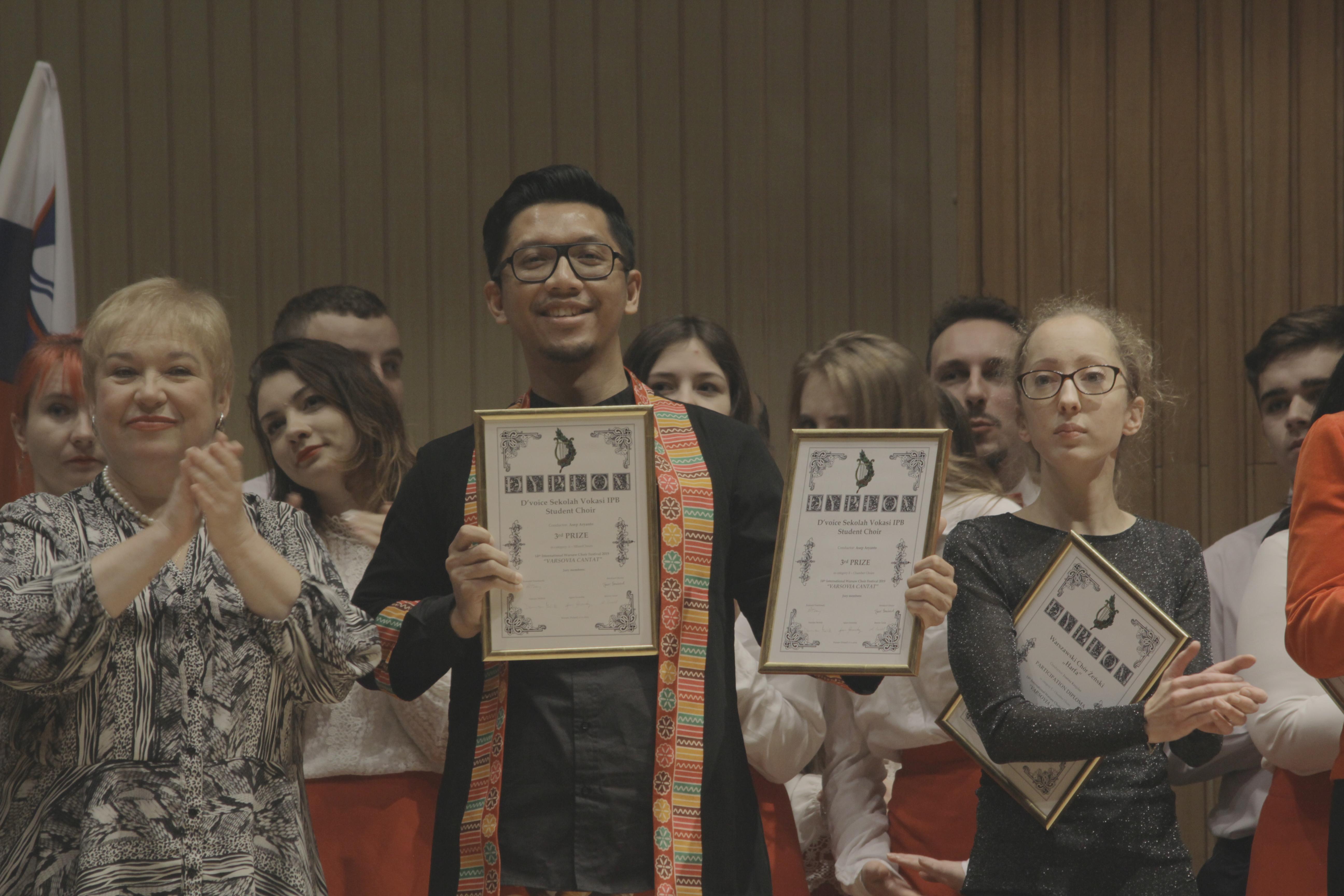 Asep Aryanto dirigen D'Voice IPB menerima penghargaan dari penyelenggara kompetisi