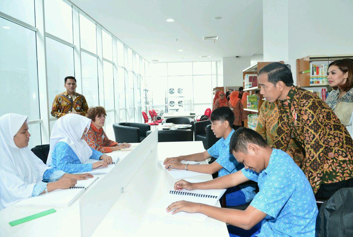 Presiden Jokowi ketika berinteraksi dengan beberapa anak tunanetra yang sedang menggunakan fasilitas Perpusnas baru ( twitter.com/kpsgoid)