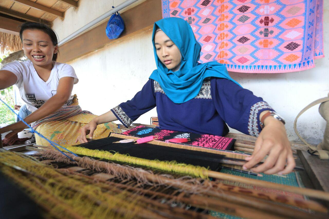 Sina (22 tahun, kiri), gadis Desa Sukarara, pusat pengrajin tenun Lombok, tengah mengajari cara menenun kepada seorang wisatawan lokal