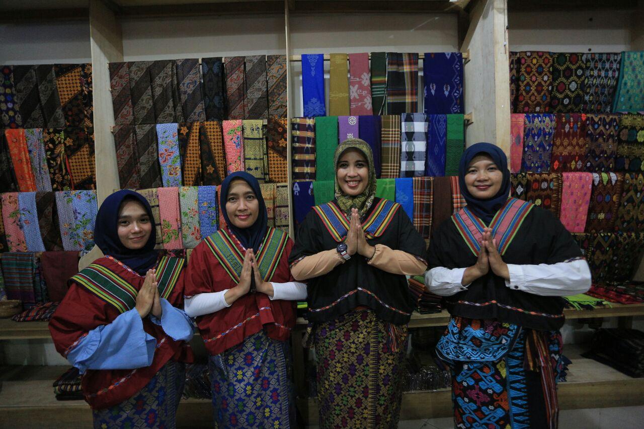 Wisatawan lokal mengenakan kain tenun khas Suku Sasak Lombok di Desa Sukarara